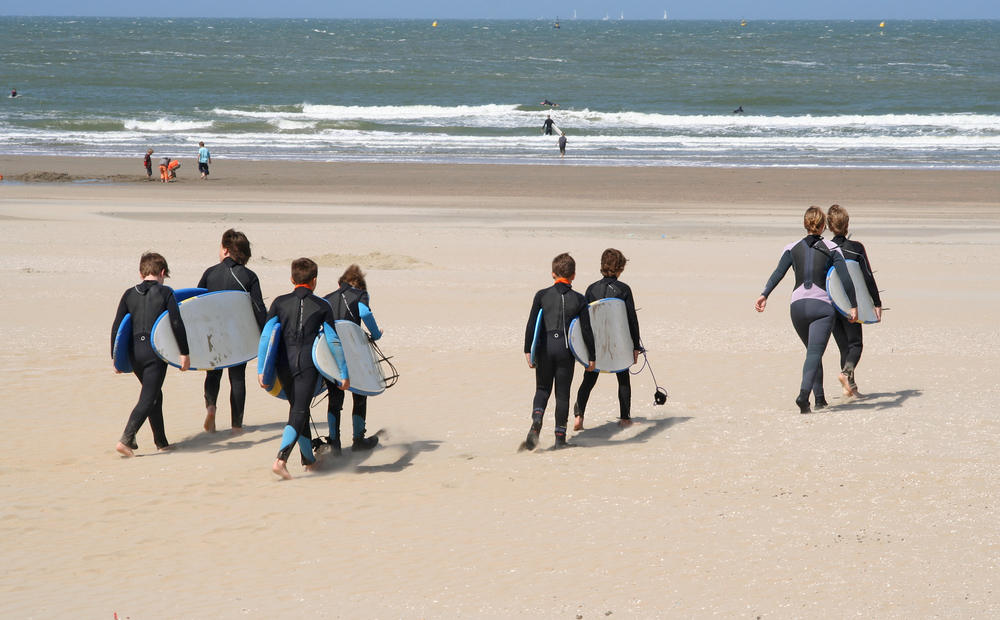 alumnos de las clases de surf llanes escuela de surf Llanes llevando las surfboards a la playa