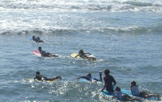 escuela surf llanes, grupo haciendo bautismo