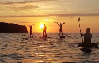 paddle surf en llanes en la puesta de sol